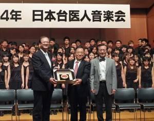 高醫校長劉景寬(左)和日本台醫人音樂會會長宮田功健(中)互贈紀念品(圖右為南杏合唱團指揮翁文國)