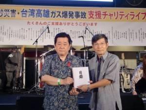 新垣直彥(左)代表主辦單位捐贈50萬日幣,盼請駐處轉交給高雄市政府