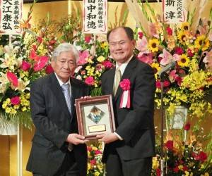 一般社團法人中華會館代表理事江夏良明(左),接受僑委會頒贈的「功在僑教」盾牌