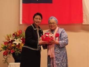 中琉文化経済協会の蔡雪泥名誉理事長(右)より記念品の花瓶を受け取る新垣社長(左)