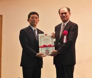 由駐橫濱辦事處處長粘信士(右)頒發當選證書,由會長羅鴻健代領