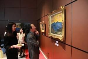 與會來賓在畫作《玉山日出》前駐足仔細欣賞