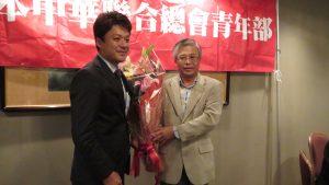 左:青年部馮明輝代表獻花給陳調和副代表