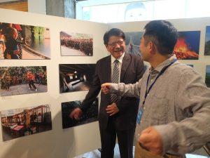 藩県長に写真の説明をするカメラマンの熊谷さん(右)