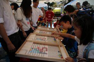 小朋友體驗台灣夜市常見的打彈珠遊戲