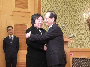 大橋会長と邱会長が笑顔で抱き合い、握手。