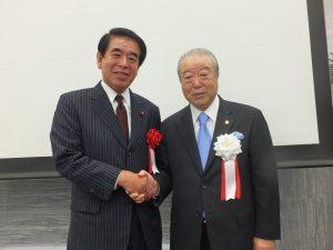 自民党東京都連の下村博文会長(左)も松本理事長に敬意を伝えた
