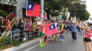 駐那霸辦事處處長蘇啟誠處和同仁與僑民及那霸日臺親善協會幹部,沿途揮舞國旗為台灣選手加油