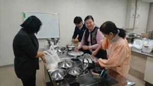 在會員張蓉容(左)指導下學習製作菜頭粿